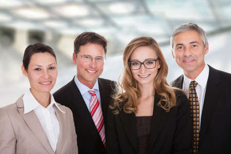 Smiling group of stylish business professionals standing in a row with their arms folded looking at the camera photo