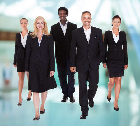 diverse hands: Group Of Happy Businesspeople Walking Towards Camera