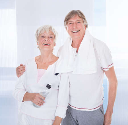 Happy Healthy Senior Couple With Towel And Water Bottle photo