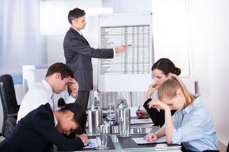 Znuděný obchodníků v prezentaci s kolegy v kanceláři