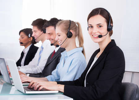Group Of Happy Businesspeople Wearing Headset Working At Office Desk photo