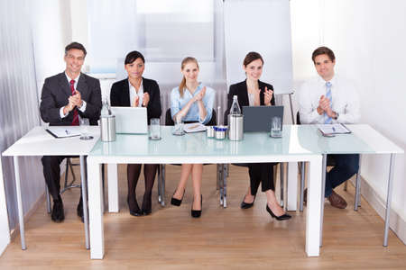 Portrait Of Happy Businesspeople Applauding In Conference photo