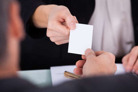 Close-up Of Businesswoman Exchanging Visiting Card With Businessman