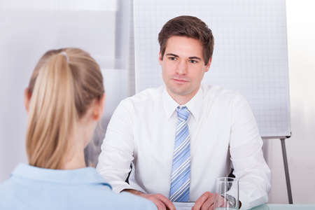 conducting: Portrait Of Young Businessman Conducting Interview In Office