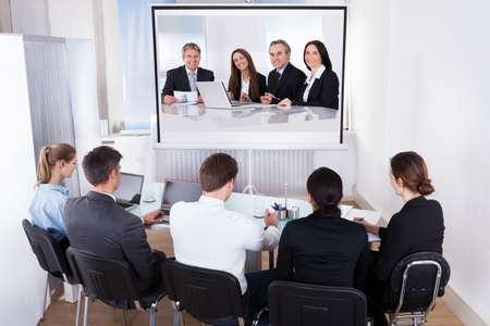 video conference: Group Of Male And Female Businesspeople At Video Conference