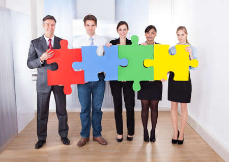 Group Of Businesspeople Holding Multi Colored Jigsaw Puzzle photo