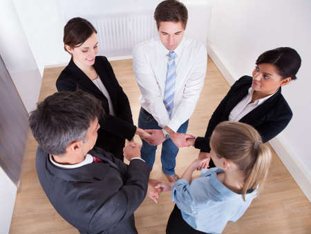 High Angle View Of Businesspeople Holding Hands photo