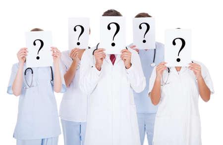 signo interrogacion: Grupo De Doctores Con Cara de ocultaci�n del signo de interrogaci�n signo m�s de fondo blanco Foto de archivo