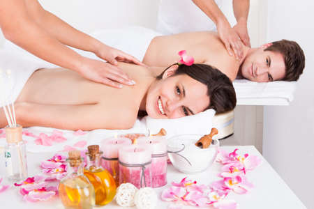 beauty saloon: Young Couple Lying Side By Side In A Spa Enjoying Tissue Back Massage Together