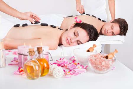beauty wellness: Mooie jonge paar met een Stone Massage In Een Spa Center Stockfoto