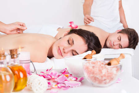adult massage: Relaxed Young Couple Receiving An Acupuncture Treatment In A Spa Center Stock Photo