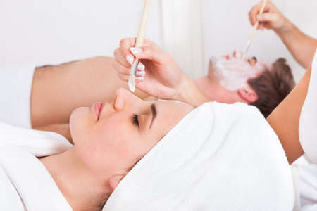 couples therapy: Therapist Applying Facial Mask To Young Couple At Beauty Salon Stock Photo