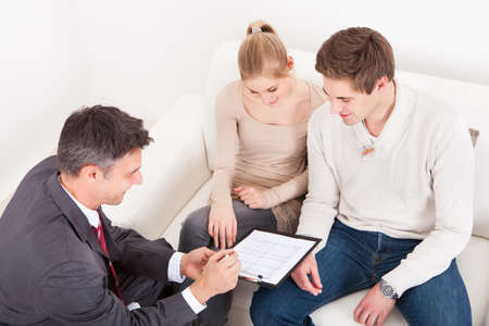 Male Consultant Showing Agreement To Young Couple At Home photo