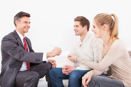legal advice: Happy Male Consultant Giving Visiting Card To Young Couple