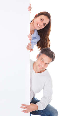 woman from behind: Happy Man And Woman Looking From Behind The Billboard Over White