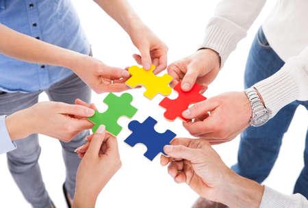 白地にカラフルなパズルを持っている 5 人の手のクローズ アップ