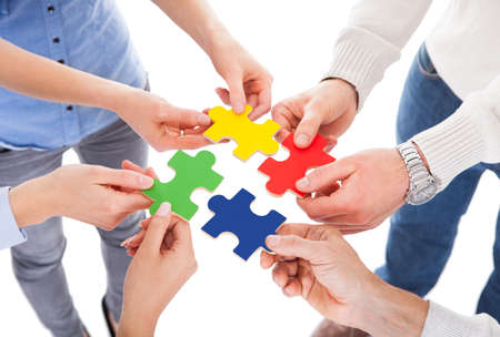 Close-up Of Five People Hand Holding Colorful Puzzle Over White Background photo