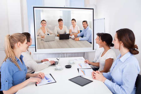 Businesspeople Sitting In Conference Room Looking At Projector Screen photo