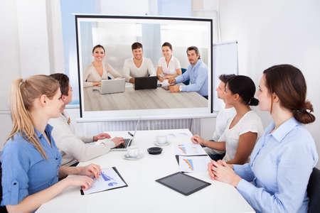 sala de reuniones: Los empresarios se sientan en sala de conferencias Mirando a la Pantalla de proyección