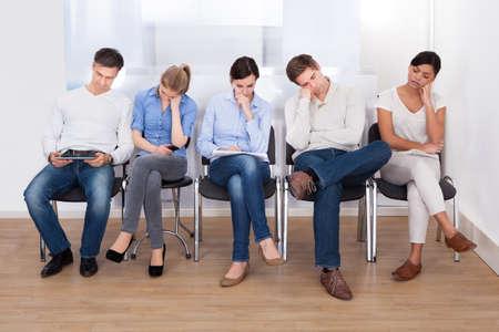 entrevista: Grupo joven de personas durmiendo en la silla en una sala de espera