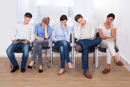 rows: Jonge groep mensen slapen op een stoel in een wachtkamer