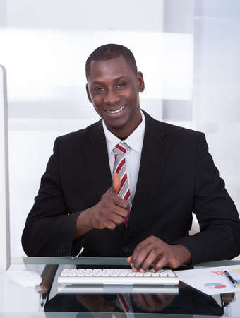 Happy Young African Businessman Using Computer At Desk Stock Photo - 25155195