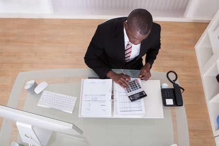 contabilidad financiera: Negocios Africano Joven Cálculo Finanzas Bills Con La Calculadora Foto de archivo