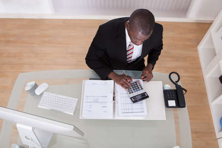 accountants: Young African Businessman Calculating Finance Bills With Calculator