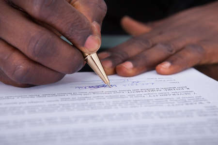 courtroom: Close-up Of An African Businessperson Signing Contract