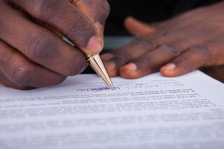 contrato de trabajo: Primer Plano De Una Firma de contrato Empresario africano