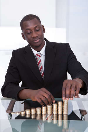 growing money: Portrait Of A Young African Businessman Stacking Coins On Desk Stock Photo