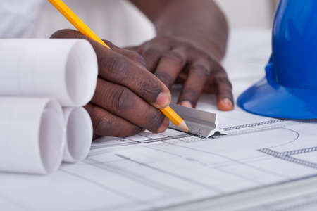 worker construction: Close-up Of An African Draftsmans Hand Drawing Blueprint Stock Photo