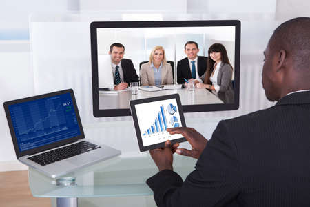 Jeune homme d'affaires Analyse graphique tout en discutant avec ses collègues Banque d'images