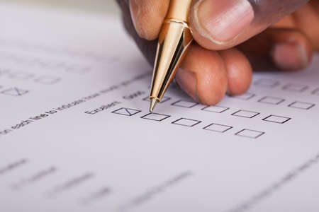 polls: Close-up Of Businessman Filling Customer Survey Form