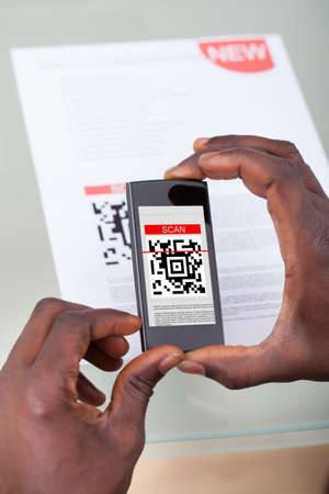 Close-up Of A Persons Hand Scanning Barcode With Cellphone photo