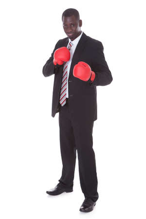 African Businessman In Boxing Gloves Over White Background photo