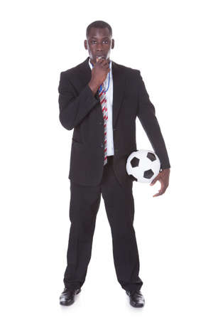 Portrait Of An African Businessman Holding Football Blowing Whistle photo