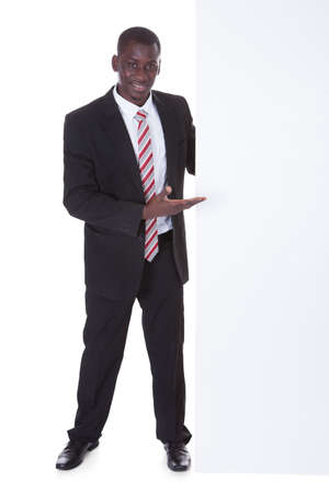 Portrait Of An African Businessman Presenting Blank Placard Over White  photo