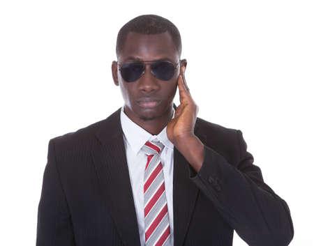 agent de sécurité: Portrait d'un jeune homme africain en costume portant des lunettes de soleil sur blanc Banque d'images