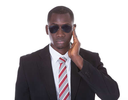 Portrait Of An African Young Man In Suit Wearing Sunglasses Over White  photo