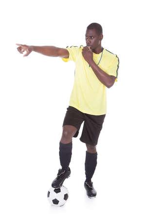 arbitro: Árbitro de fútbol que sopla del silbido con la pierna en bola sobre blanco