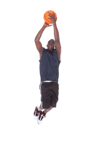 Young African Man Jumping With Basketball Over White  photo