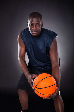 African Young Man With Basketball Over Black  photo