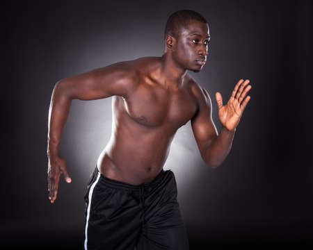 Portrait Of Young African Man Jogging On Black Background photo