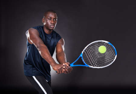 Portrait Of Young African Man Playing Tennis On Black  photo