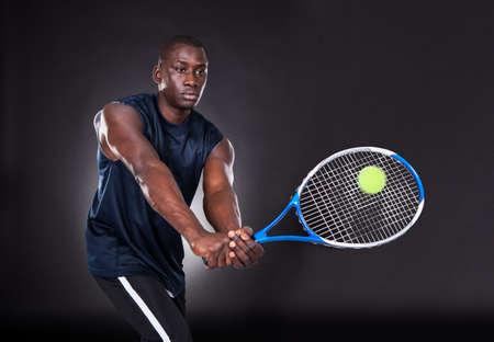 jugando tenis: Retrato del hombre africano joven que juega al tenis En Negro Foto de archivo