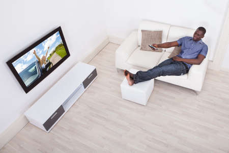 African Man Sitting On Sofa With Remote Holding In Hand photo
