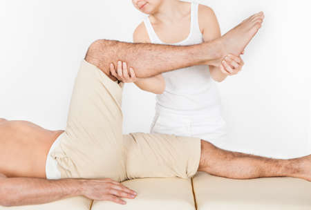 Young Man Lying On Table Getting Foot Massage From Masseuse photo