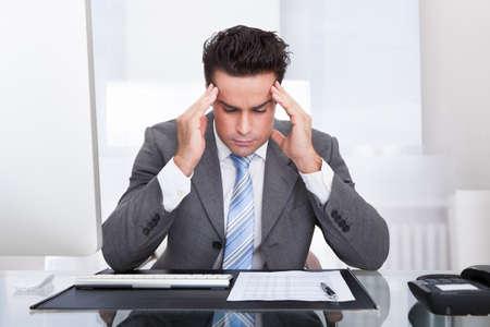 Portrait Of A Stressed Businessman Sitting At Desk photo