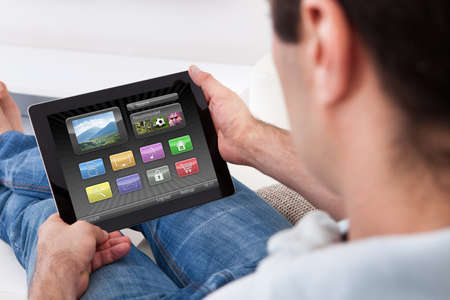 Close-up Of Man Hands Holding Tablet Pc Showing Icons photo